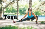 Sporty woman doing stretching exercise outdoors in park and looking at camera